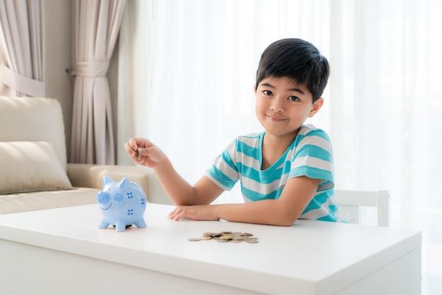 Il piccolo ragazzo asiatico inserisce una moneta nel porcellino salvadanaio blu in tavola bianca al salone a casa per il risparmio del bambino. Foto Premium