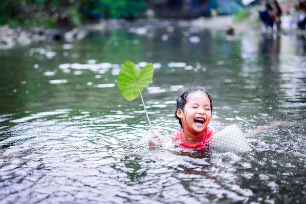 Piccola ragazza asiatica che gioca acqua con foglia di loto nel flusso naturale Foto Premium