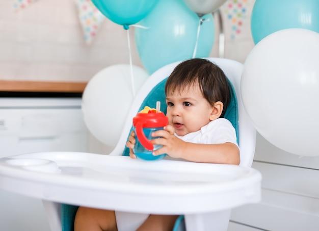 Piccolo neonato seduto nel seggiolone blu a casa sulla cucina bianca e acqua potabile dalla tazza sippy su sfondo con palloncini. Foto Premium