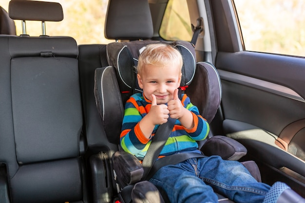Piccolo neonato seduto su un seggiolino per auto allacciato con il pollice in alto in macchina. Foto Premium