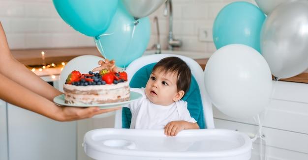 Piccolo neonato seduto nel seggiolone in cucina bianca e degustazione di torta del primo anno con frutta dalle mani della madre su sfondo con palloncini. Foto Premium