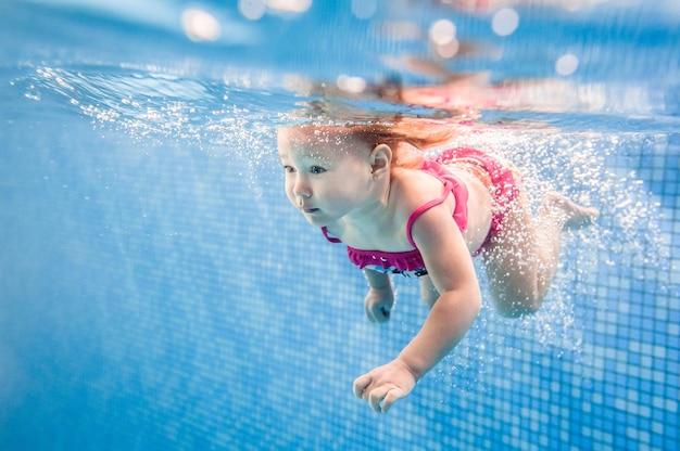 Piccolo bambino, ragazza che nuota sott'acqua nella piscina per bambini. bambino subacqueo. imparare a nuotare. goditi il nuoto e le bolle. Foto Premium