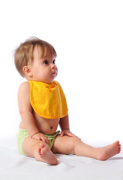 Piccola neonata con il bavaglino che guarda l'obbiettivo e acqua potabile o composta dalla tazza Foto Premium