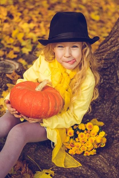 Piccola bella ragazza con i capelli biondi con grande zucca in autunno. halloween Foto Premium