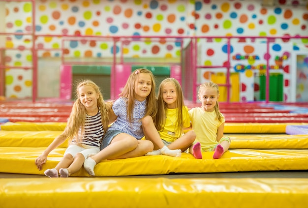 Le piccole ragazze sorridenti bionde si siedono insieme sul trampolino giallo Foto Premium