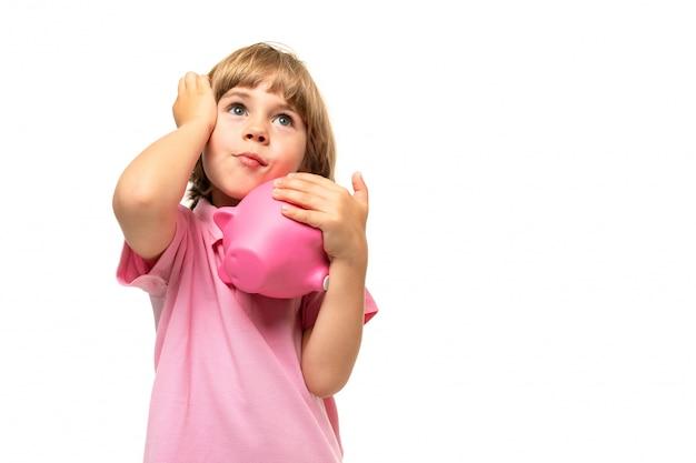 Ragazzino in una maglietta rosa con un salvadanaio su uno sfondo bianco Foto Premium