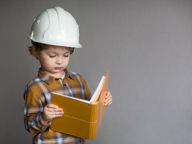 Ragazzino in casco protettivo, bambino con capanna di ingegneria, edificio in via di sviluppo costruzione e concetto di architettura Foto Premium