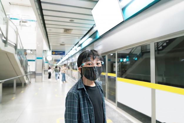 Un bambino indossa uno scudo facciale e maschere per la salute per viaggiare con i mezzi pubblici. Foto Premium