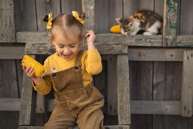 Una bambina allegra si siede su una scala di legno e mangia il mais. il gattino è seduto accanto al bambino. Foto Premium