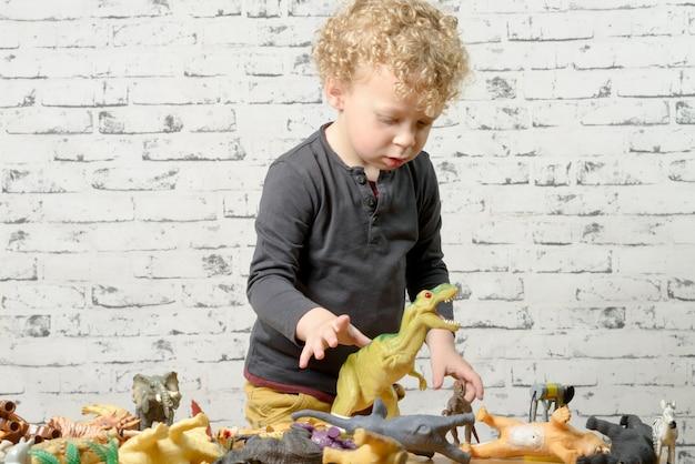 Un bambino gioca con animali giocattoli Foto Premium