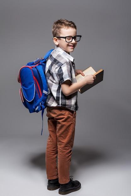 Piccolo bambino con la borsa di scuola e il libro. giovane allievo con zaino e libro di testo Foto Premium