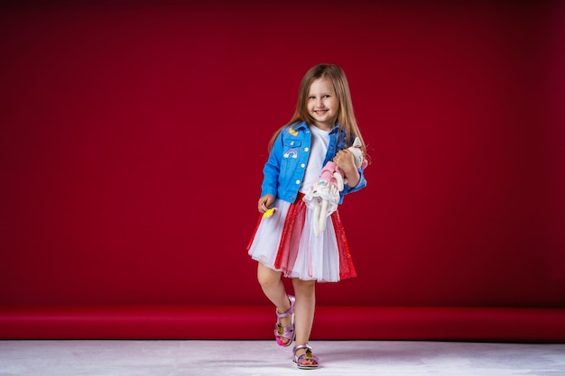 Piccola ragazza carina in abiti alla moda che abbraccia il suo animale giocattolo preferito Foto Premium