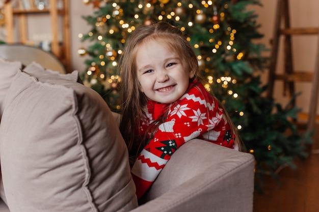 La piccola ragazza sveglia in maglione rosso di natale gioca dall'albero di natale a casa. decorazione di capodanno. Foto Premium