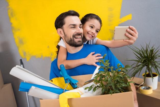 La piccola figlia che per mezzo dello smartphone fa il selfie con suo padre Foto Premium