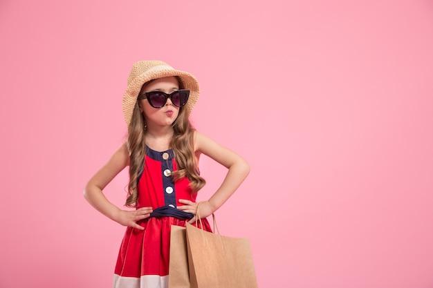 Piccola fashionista con una borsa della spesa in cappello estivo e occhiali da sole, sfondo rosa colorato, il concetto di moda per bambini Foto Premium