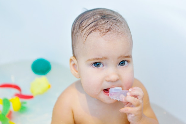 Una bambina si lava i denti in bagno. ritratto di un bambino con uno spazzolino da denti Foto Premium