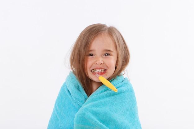 Una bambina si lava i denti su uno sfondo bianco. ritratto di un bambino con uno spazzolino giallo. asciugamano blu intorno al collo. Foto Premium