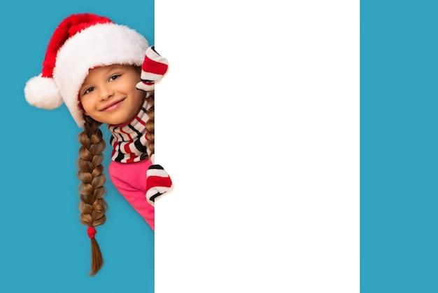 Una bambina in un cappello di natale e guanti guarda da dietro uno sfondo bianco. Foto Premium