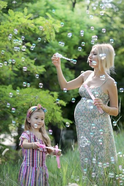 Bambina e sua madre incinta che giocano a soffiare bolle di sapone, concetto di infanzia felice, foto all'aperto Foto Premium