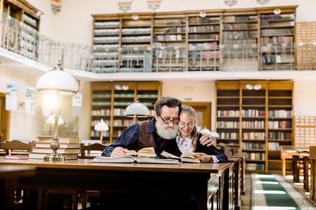 Una bambina e suo nonno barbuto senior stanno leggendo libri, seduti al tavolo con molti libri e lampada da scrivania vintage nella vecchia biblioteca antica Foto Premium