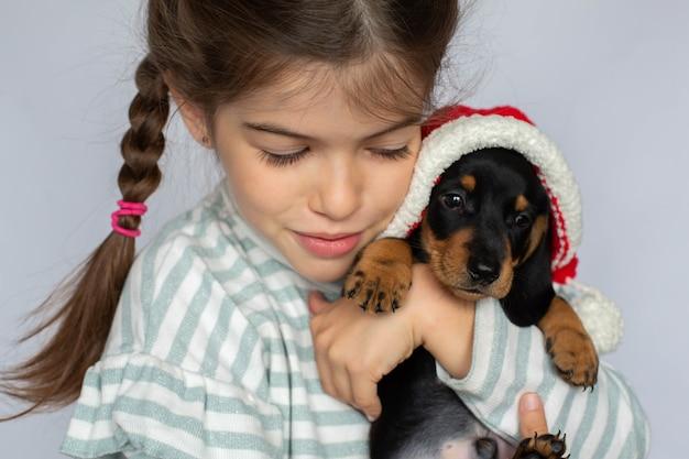 Bambina che tiene un cucciolo di bassotto nel suo regalo di capodanno per animali da compagnia Foto Premium