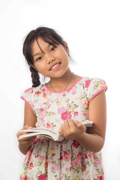 La bambina è soddisfatta del libro su un bianco Foto Premium
