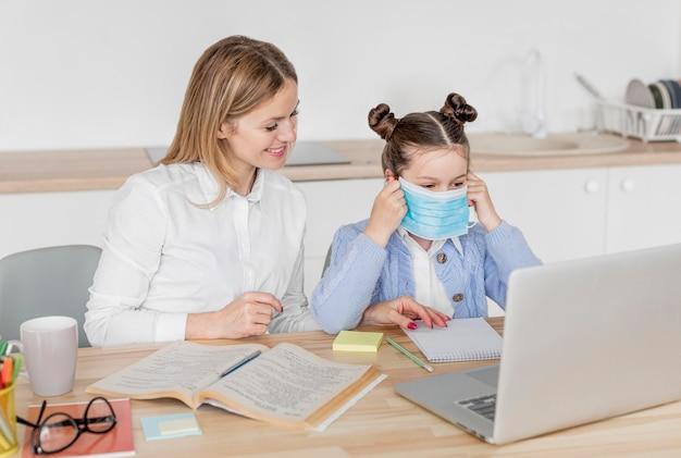 Bambina che indossa una maschera medica in una classe online Foto Premium