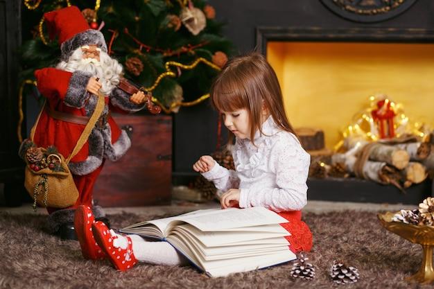 Bambina seduta sul pavimento in bellissime decorazioni natalizie Foto Premium