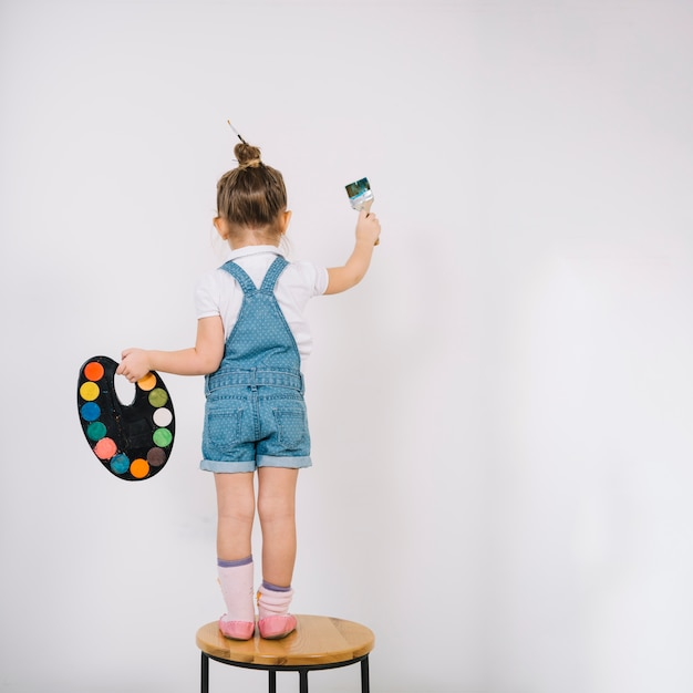 Bambina che sta sulla sedia e che dipinge parete bianca con la spazzola Foto Premium