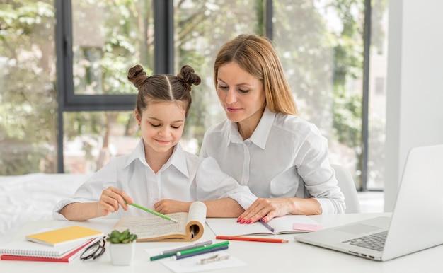 Bambina che studia a casa con il suo insegnante Foto Premium