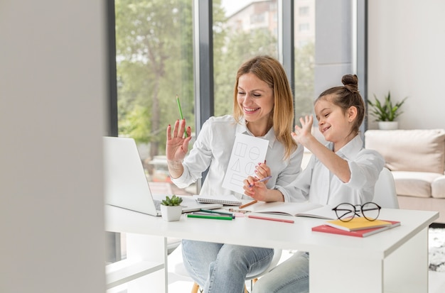Bambina che studia con il suo insegnante all'interno Foto Premium