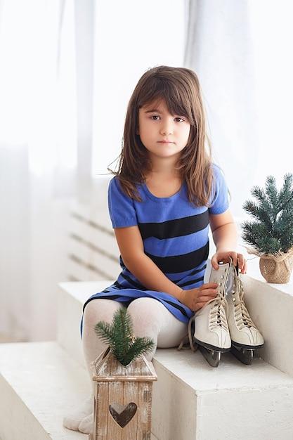 Bambina che prova su un pattinaggio su ghiaccio di grandi dimensioni. ragazzino e pattini Foto Premium