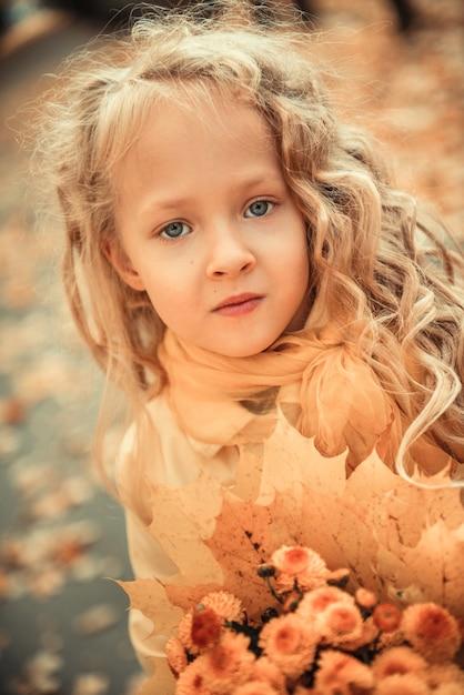 Bambina con capelli biondi in autunno sfondo con fiori gialli Foto Premium
