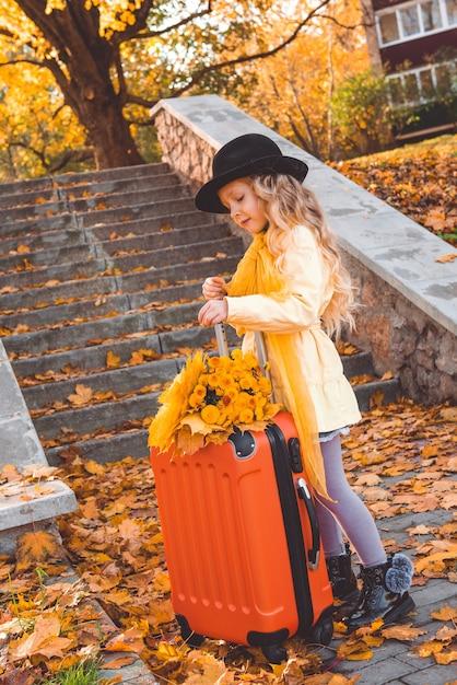 Bambina con capelli biondi in autunno con fiori e valigia Foto Premium