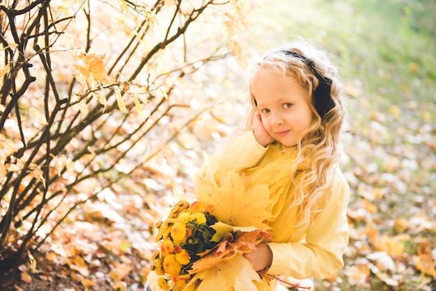 Bambina con capelli biondi in autunno con fiori gialli Foto Premium