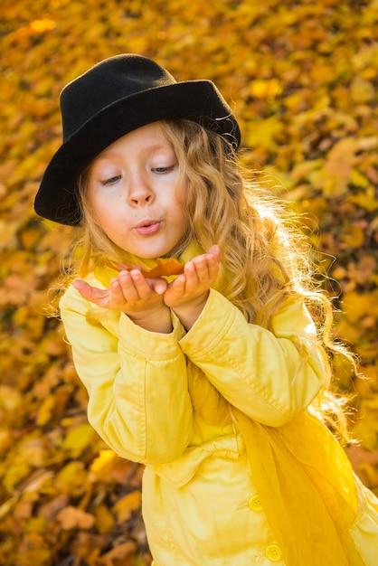 Bambina con capelli biondi in autunno con foglia gialla Foto Premium