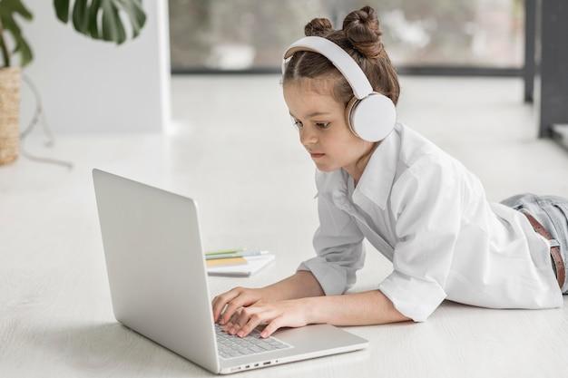 Bambina con le cuffie che ascolta il suo insegnante Foto Premium