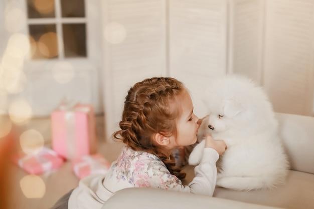 Bambina con cuccioli bianchi e scatole regalo Foto Premium