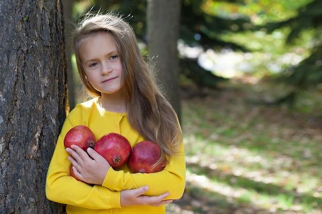 Bambina in una giacca gialla si trova nel parco e tiene melograni maturi. Foto Premium
