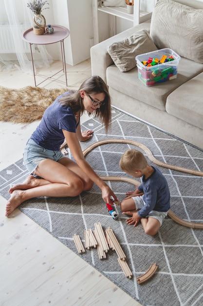 Ragazzino e sua madre che giocano con la ferrovia che si siede sul pavimento Foto Premium