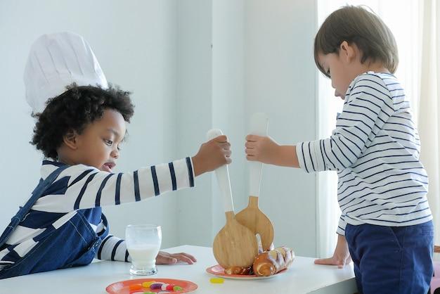 Piccoli bambini adorabili che giocano con una cucina giocattolo indossando il cappello da chef. giocattoli educativi per bambini. Foto Premium