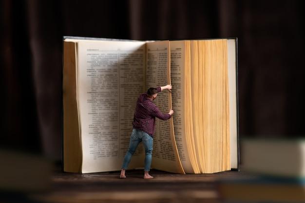 Omino gira la pagina di un grande libro, effetto scala. acquisire conoscenza e istruzione, leggere il concetto. Foto Premium