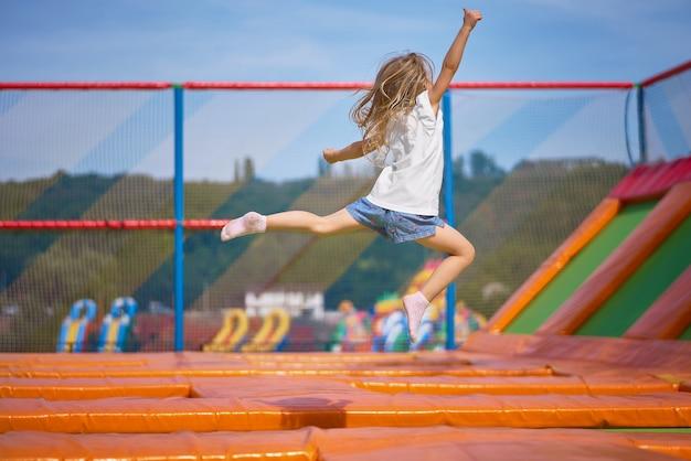 Divertiresi grazioso della bambina all'aperto. saltando sul trampolino nella zona dei bambini. ragazza felice che salta sul trampolino giallo nel parco divertimenti Foto Premium