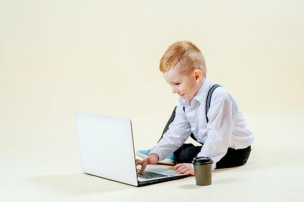 Ragazzino dai capelli rossi in un tailleur con un telefono in mano si affretta a una riunione in tailleur, affari, mini capo Foto Premium