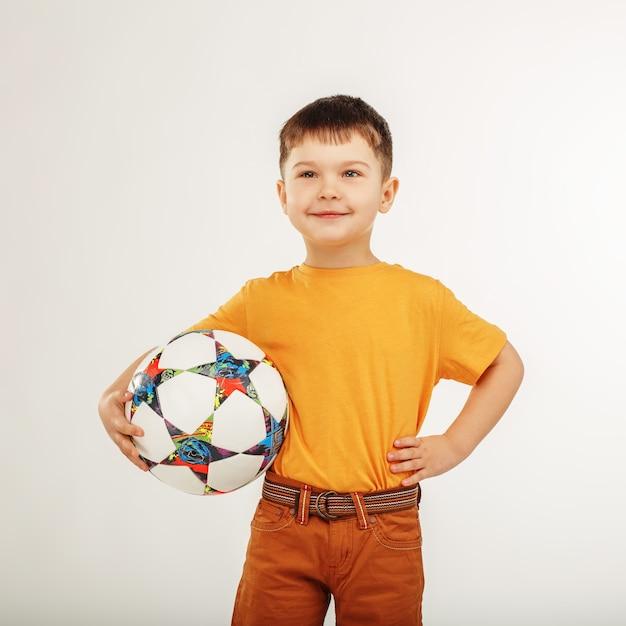 Piccolo ragazzo sorridente che tiene un pallone da calcio sotto il braccio Foto Premium