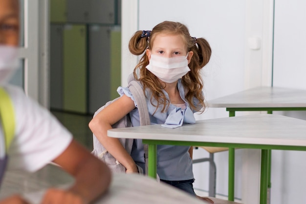 Piccolo studente che indossa una mascherina medica Foto Premium