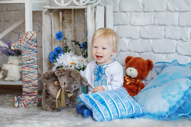Ragazzo biondo di un anno in camicia ricamata ucraina tradizionale che gioca con i giocattoli nello studio decorato Foto Premium