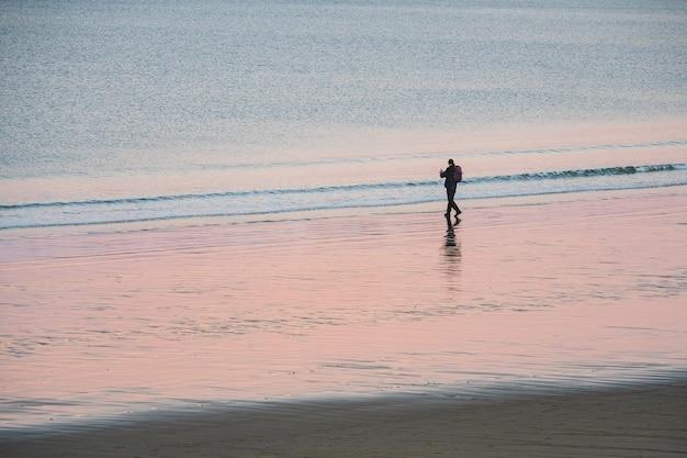 Un turista solitario con uno zaino riprende un meraviglioso paesaggio artico al tramonto sull'oceano Foto Premium