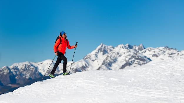 Una donna sola cammina sulla neve con i ramponi Foto Premium