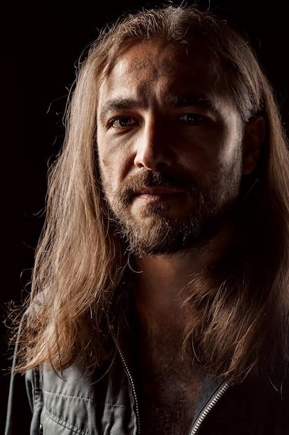 Uomo di mezza età maschile dai capelli lunghi in piedi nel buio si chiuda Foto Premium